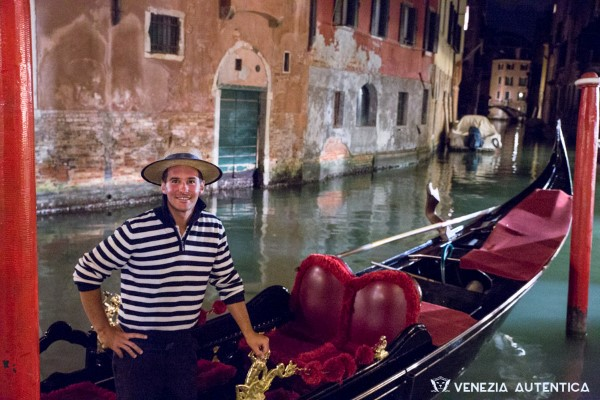Young gondoliere in Venice smiling from his gondola at the camera on a spring night. The canal unwinds in the background, passing under a bridge.