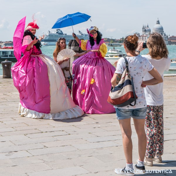 Two cheaters posing with fake pink costumes taking a picture with a tourist. In the foreground, two friend of the tourist taking the picture. In the background, a big ship or grande nave. Small picture