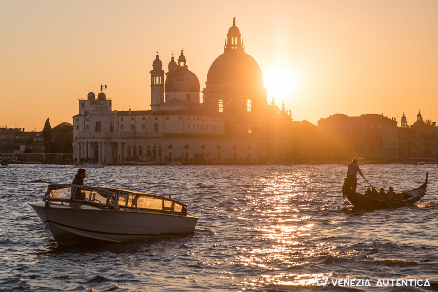White taxi boat and gondola at sunset on the saint mark's basin in Venice. In the background, the backlit Salute church and the punta della dogana