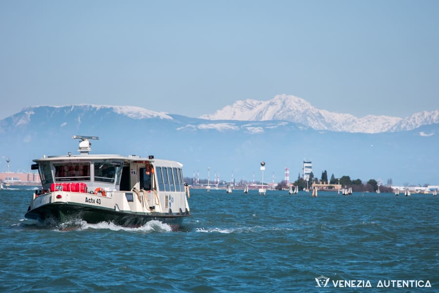 A public water bus navigating in front of the fondamenta nuove on a clear day, with snowy dolomites in the background.