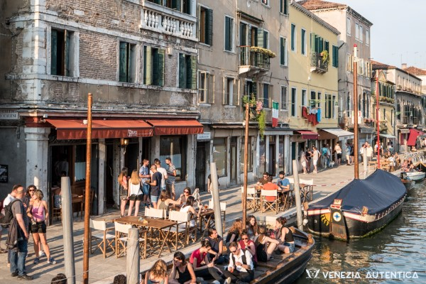 People on the fondamenta degli Ormesini in Venice (Italy) chatting or seating on boats in front of the bar Al Timon on a summer evening. Small Imager