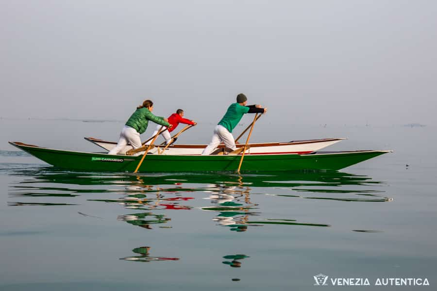 Venetians rowing a sandolo, a traditional Venetian rowing boat on the flat and calm waters of lagoon of Venice.