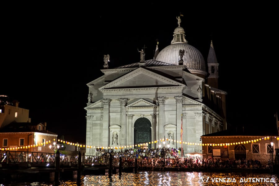 Picture taken from the water of the Redentore church on the night of the redentore celebration. Crowd of people on the fondamenta della giudecca along the water, as well as on the square in fron of the church and on the steps leading to the entrance