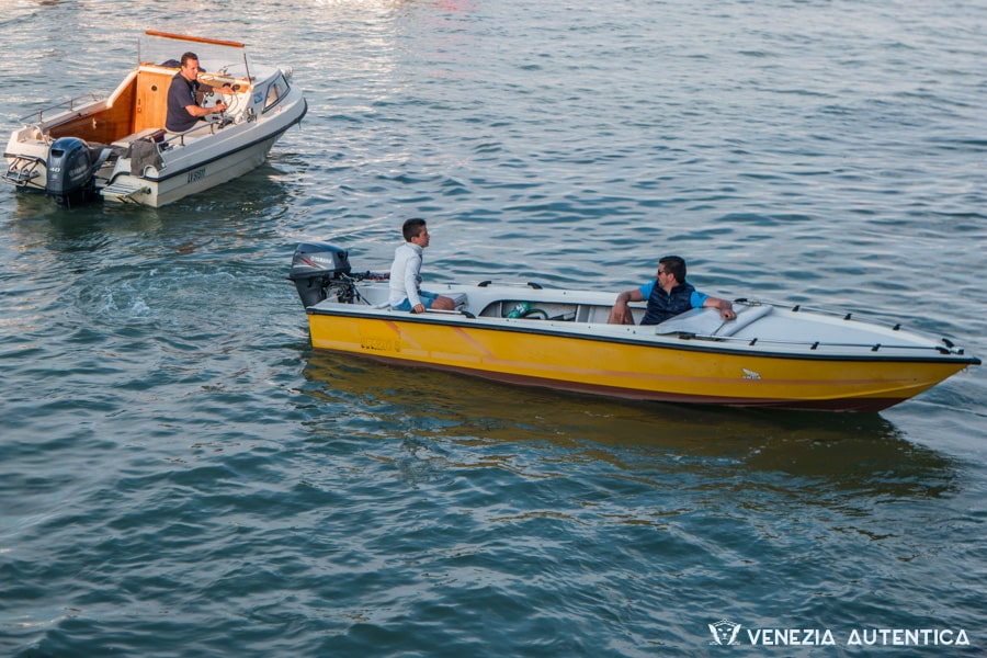 Venetian kid driving a yellow and white motor boat while under the surveillance of an adult. A half cabin cruiser in the background. Water all around.