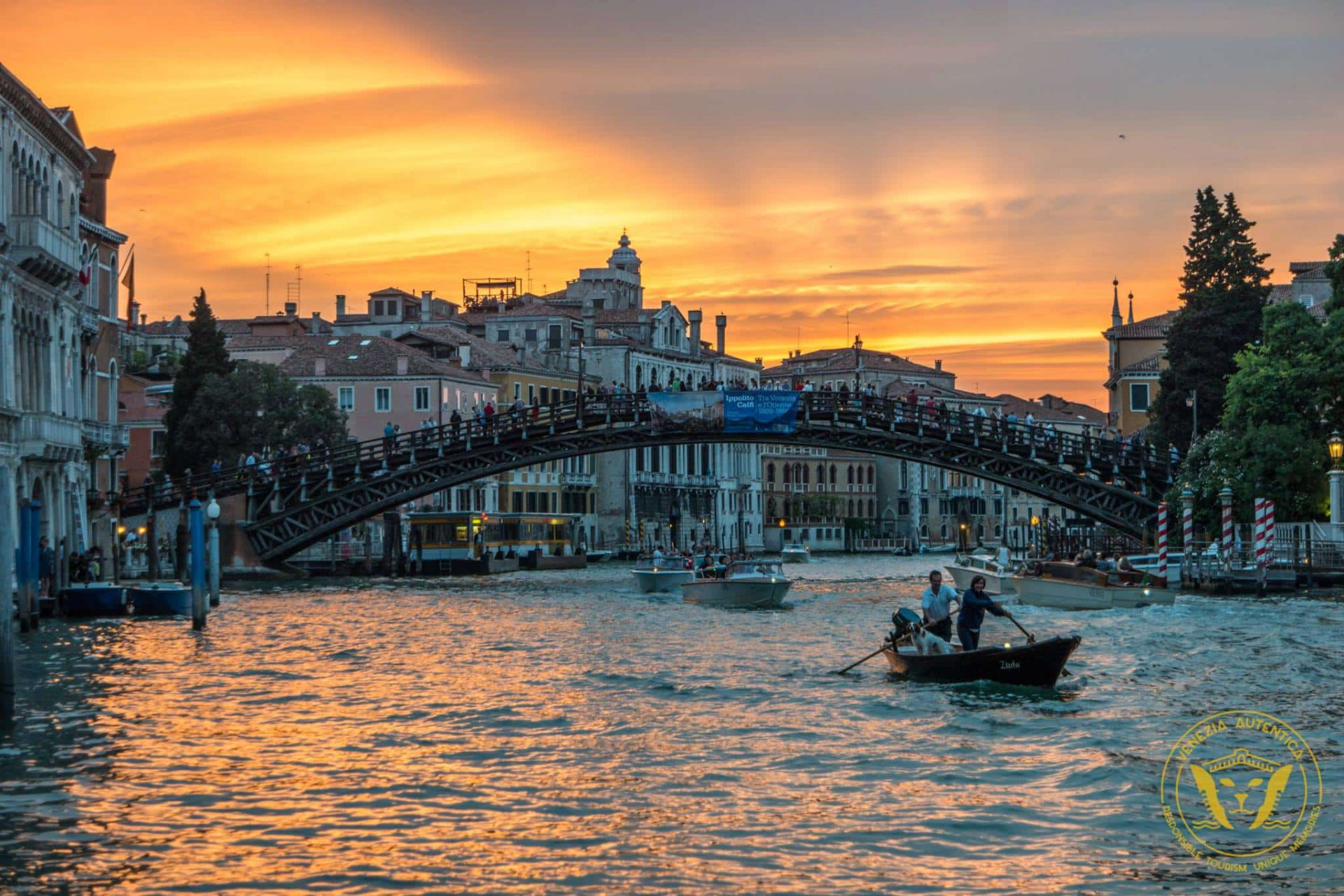 Venetians on a rowing boat on the grand canal in Venice, Italy, at sunset