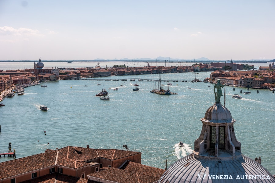 View from the top of the San Giorgio bell tower of the Giudecca Canal and the bridge of barges crossing the canal and connecting the fondamenta delle zattere to the chiesa del redentore. In the foreground, Saint George's statue can be seen on top of the San Giorgio church dome.