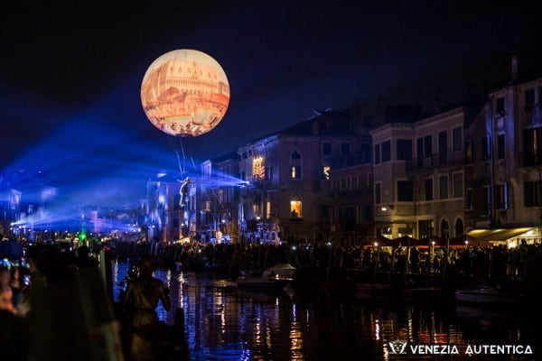 Acrobatic dancer flying over a Canal in Venice at night during Carnival