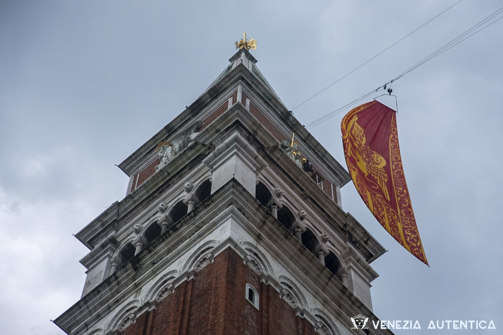 A big Venice flag, characterised by a winged lion, is lifted on top of the Sain Mark's Bell Tower.