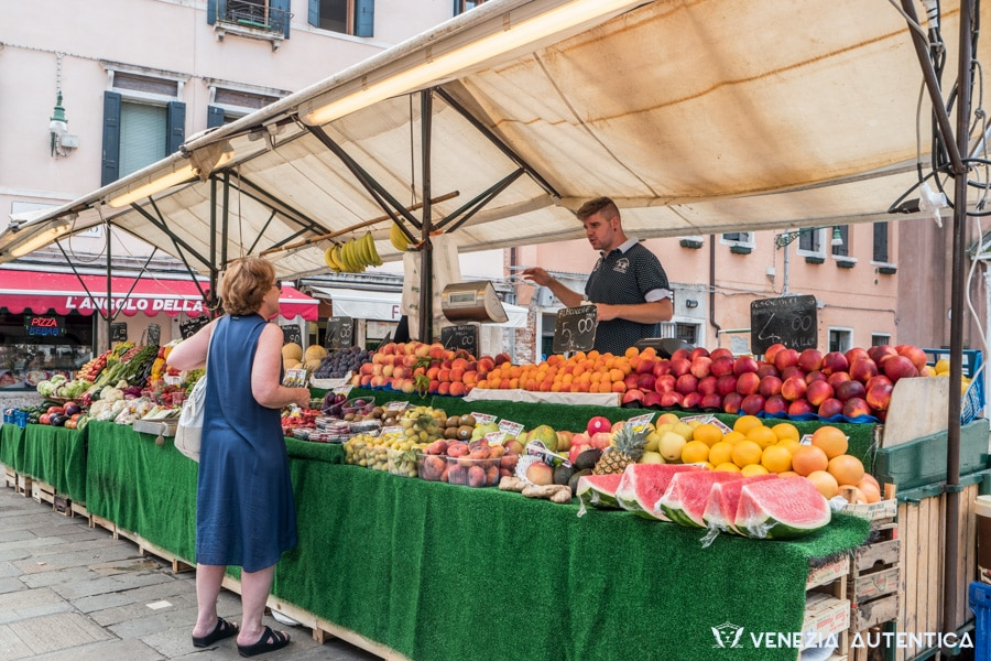 San Leonardo fruit and vegetables market in Venice. Marco is serving a fond customers at his stand. Fresh watermelons, peaches, apples and many other fruits and vegetables nationally or locally produced