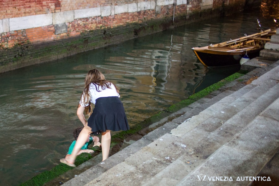 A tourist in a canal after slipping on a slippery green step in Venice