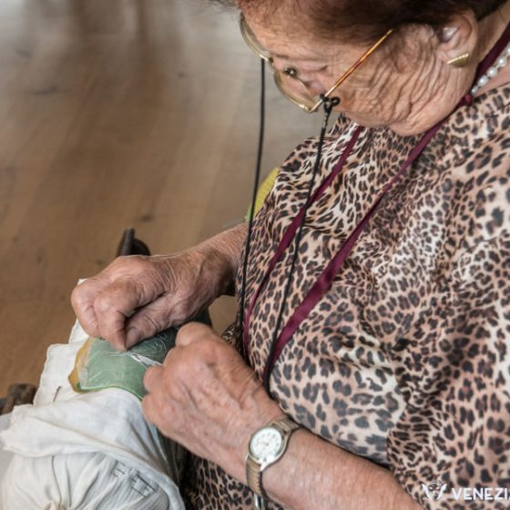 Expert hands working merletto at the Burano Lace Museum