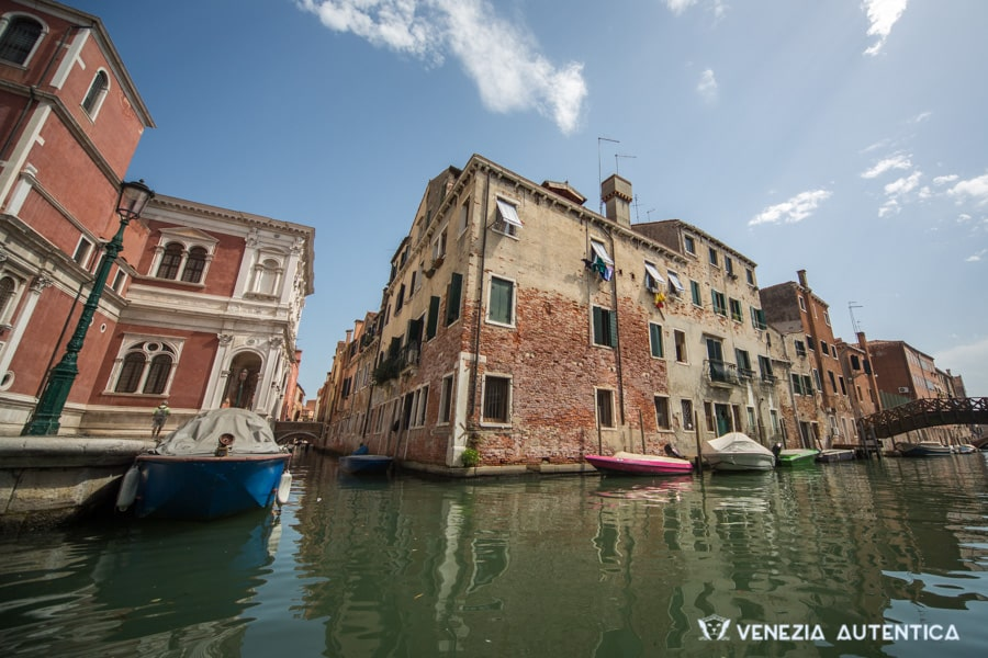 A view of a corner of Venice, from a canal, on a bridgt sunny day