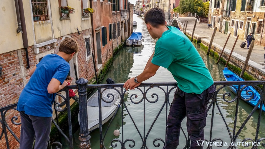 Children retrieving their football from a canal in Venice, Italy