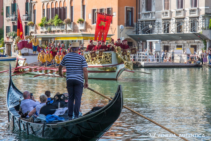 A gondola in front of the Royal Barge on the Grand Canal. Warm weather and beautiful sun on the day of the Historical Regatta