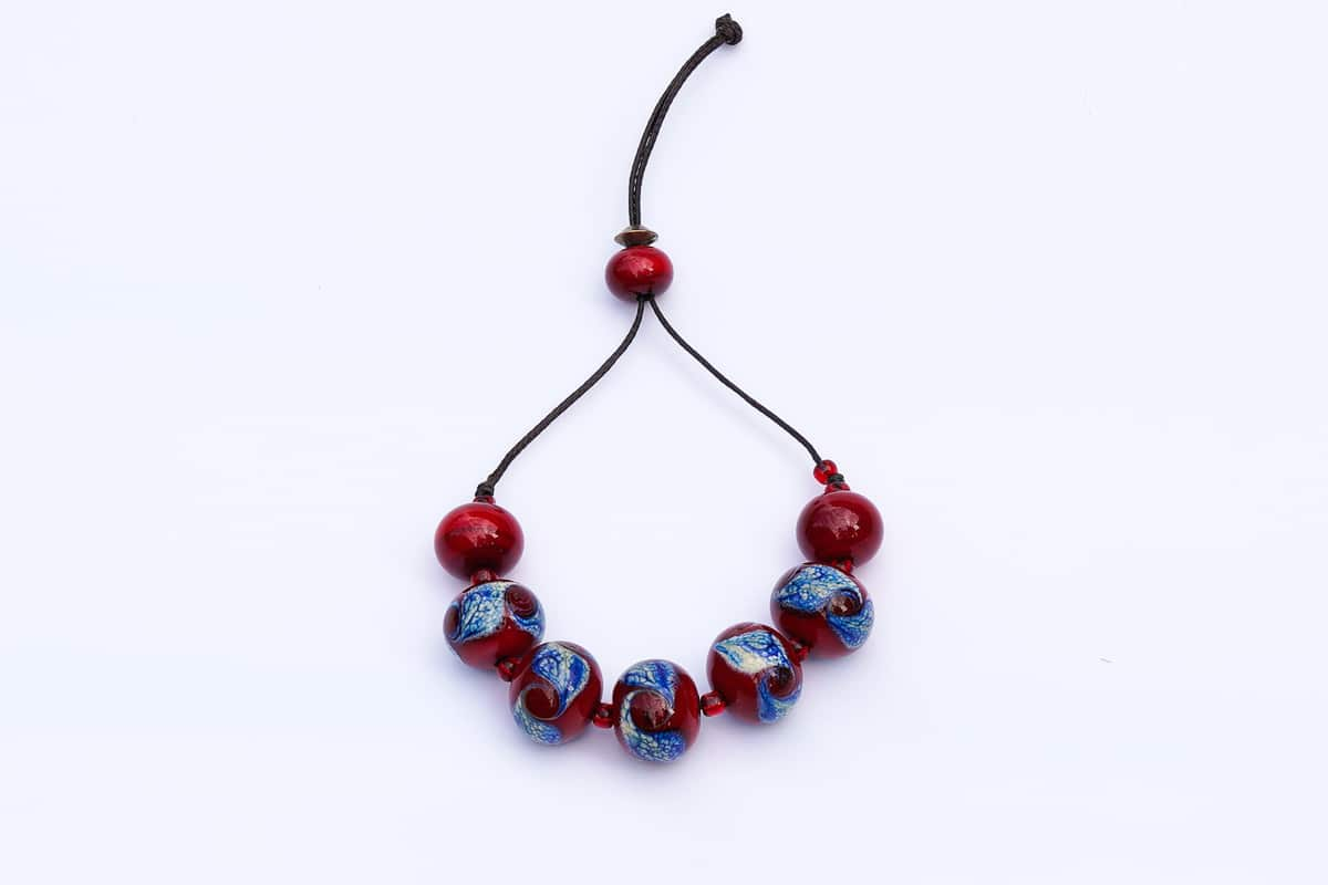 """Blue Swirls in a Cherry Sea"" Bracelet Shop by Venezia Autentica - Shop by Venezia Autentica - Stunning Murano Glass bracelet, handmade in Venice, with mesmerizing red and blue beads. Every bead, crafted by lampworking, is unique, beautiful, and durable."